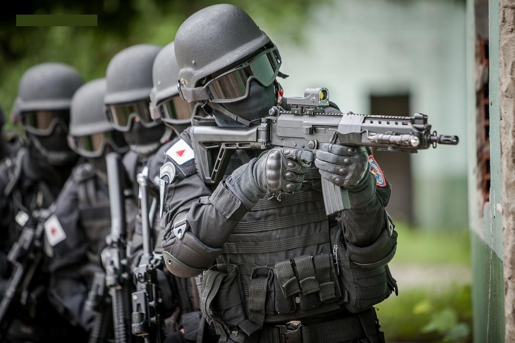 שוטרים מכוסים מכף רגל ועד ראש בציוד לוחמה וקסדות ואחד מהם מכוון נשק אוטומטי למקום שאינו נראה בתמונה